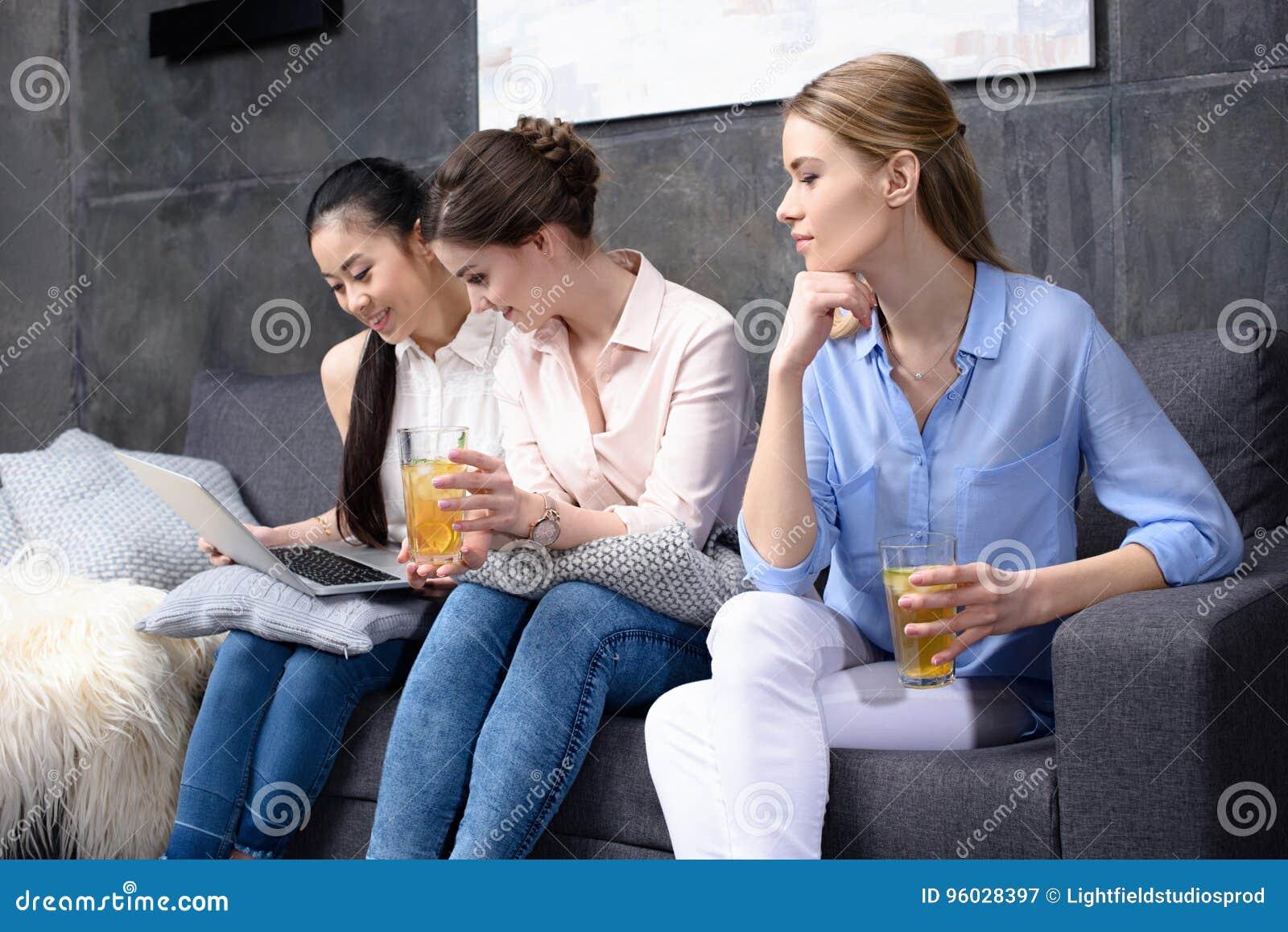 Przyjaciele używa laptop podczas gdy wydający czas wpólnie