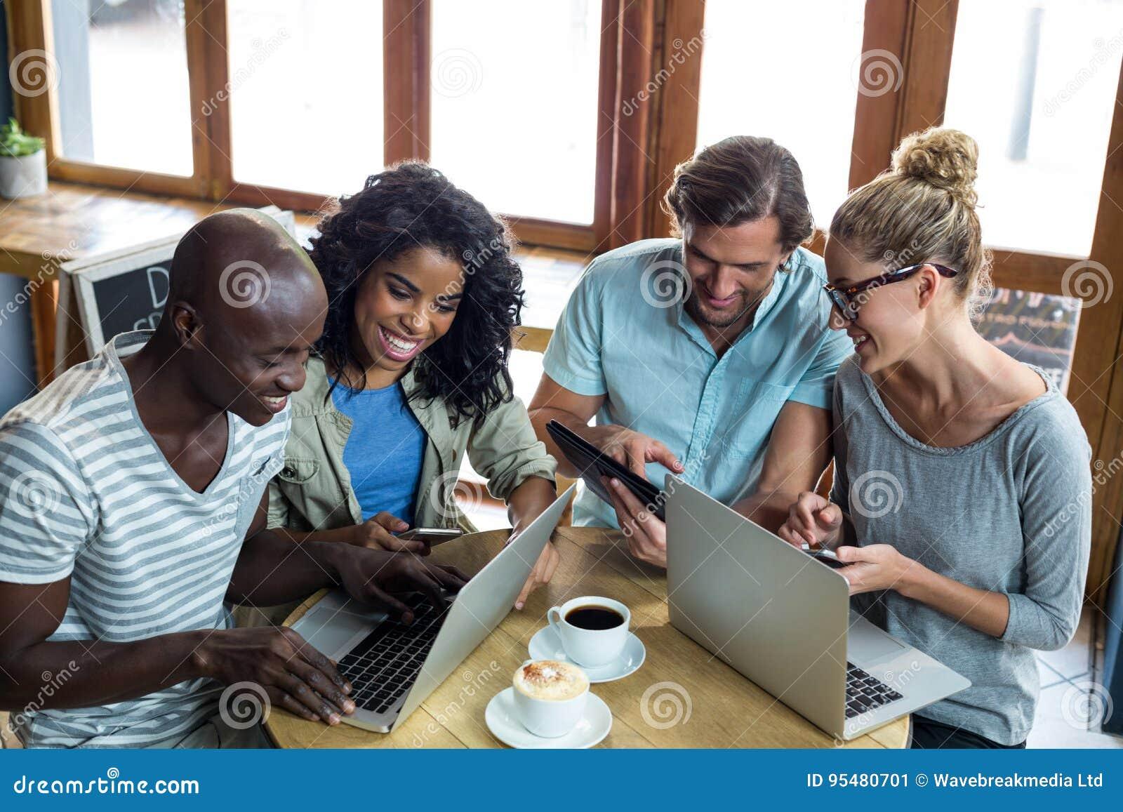 Przyjaciele używa laptop, telefon komórkowego i cyfrową pastylkę, podczas gdy mieć kawę
