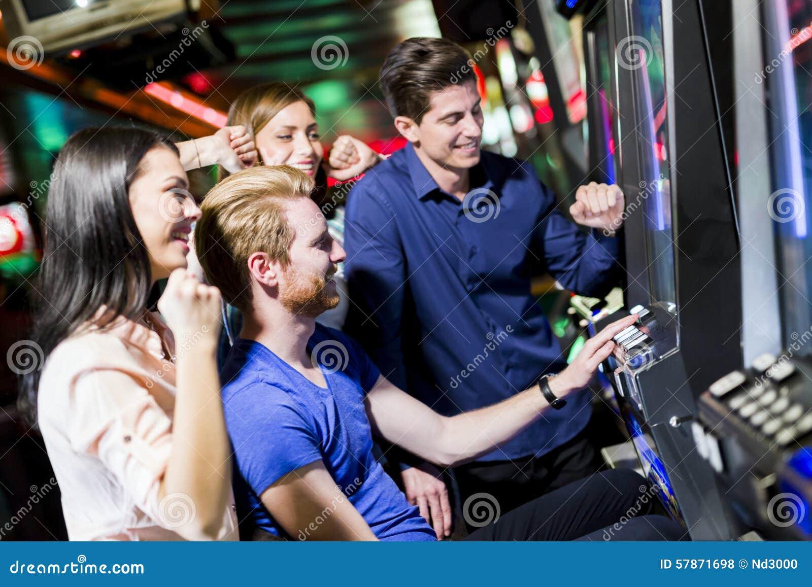 Przyjaciele uprawia hazard w kasynowej bawić się szczelinie różnorodnych maszynach i