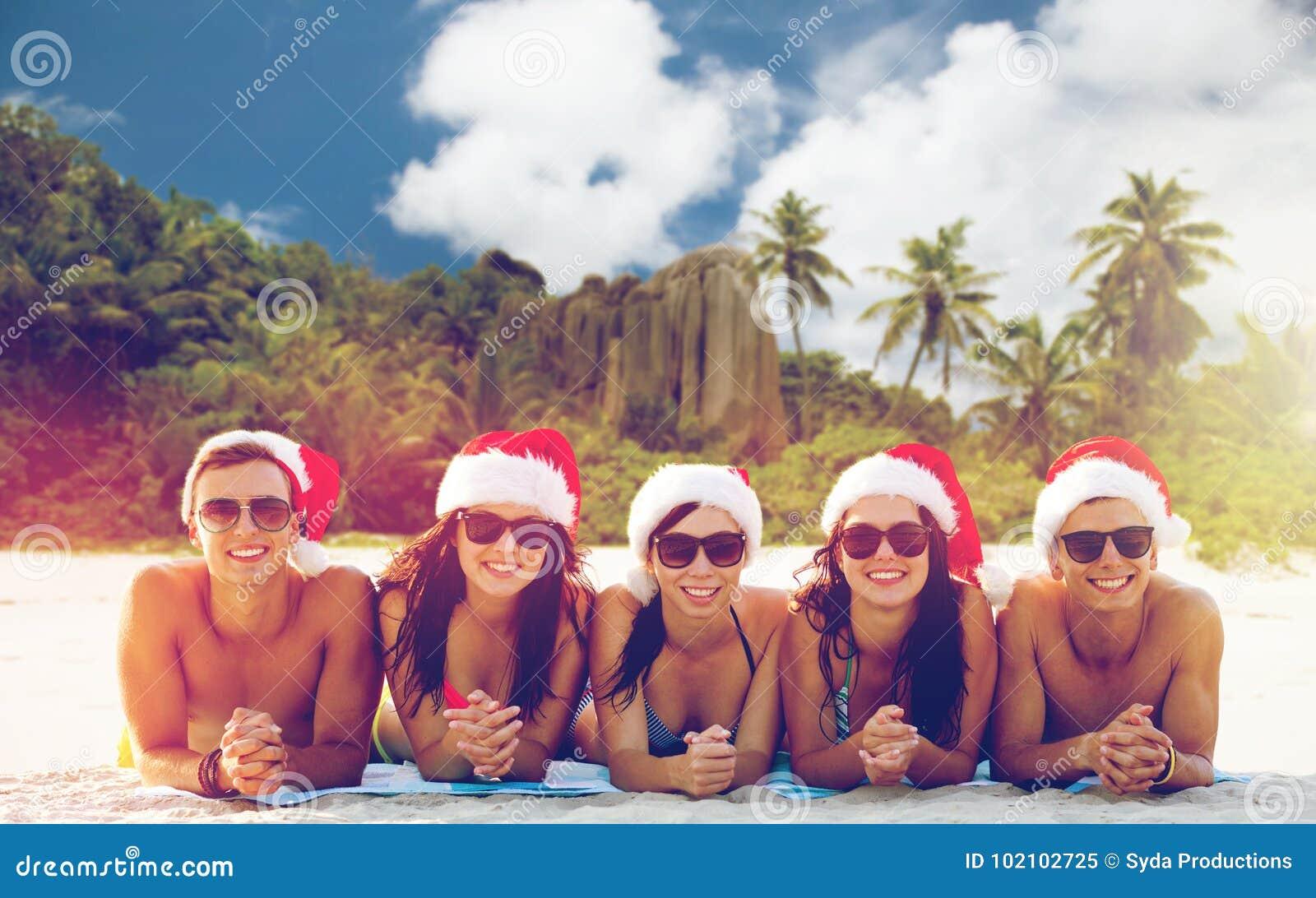 Przyjaciele w Santa kapeluszach na plaży przy bożymi narodzeniami