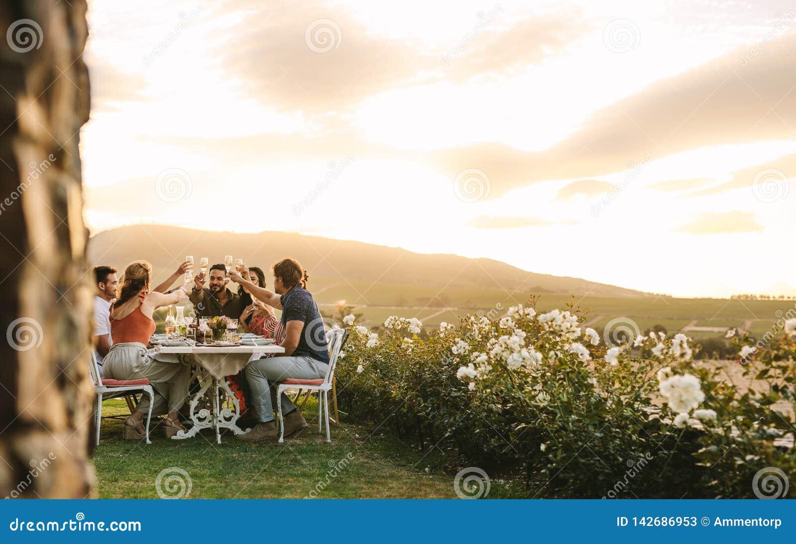 Przyjaciele wznosi toast szampana przy obiadowym przyjęciem