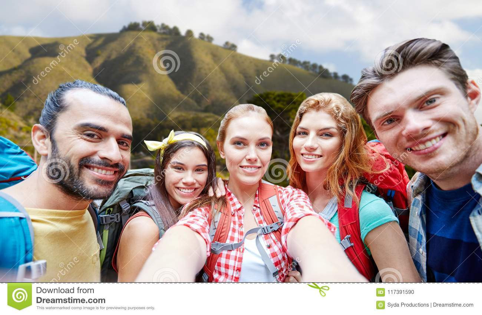 Przyjaciele z plecakiem bierze selfie nad dużym sura