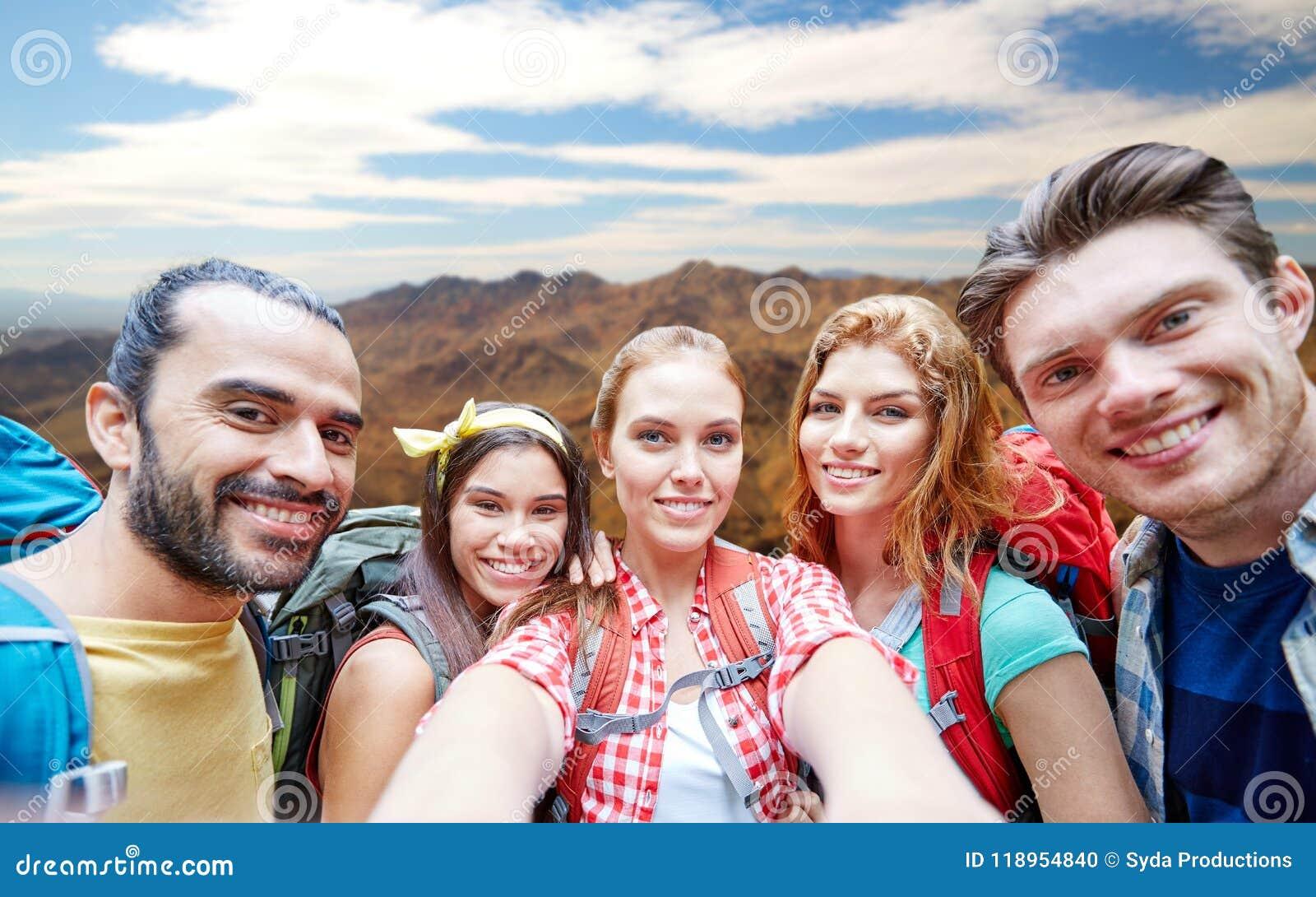 Przyjaciele z plecakiem bierze selfie ove góry