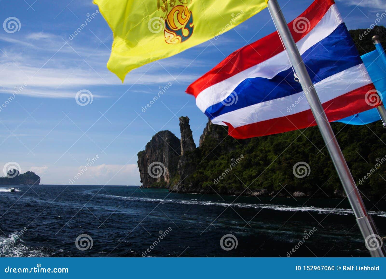 Przyjeżdżać na tropikalnym wyspy Ko Phi Phi z promem od Phuket - Zamyka w górę Tajlandzkiego chorągwianego falowania od łodzi z s