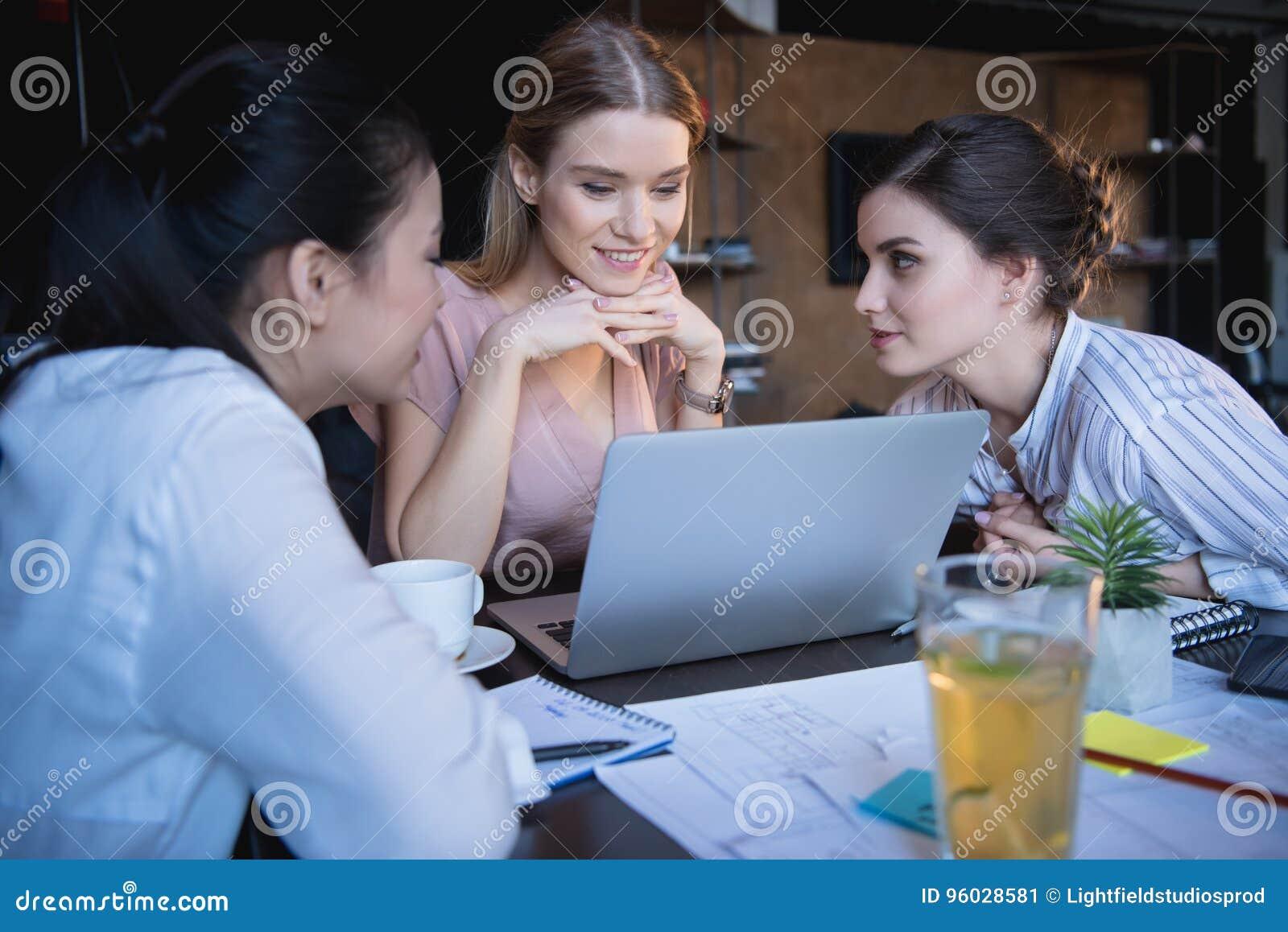 Przypadkowi bizneswomany pracuje na laptopie przy biurem wpólnie