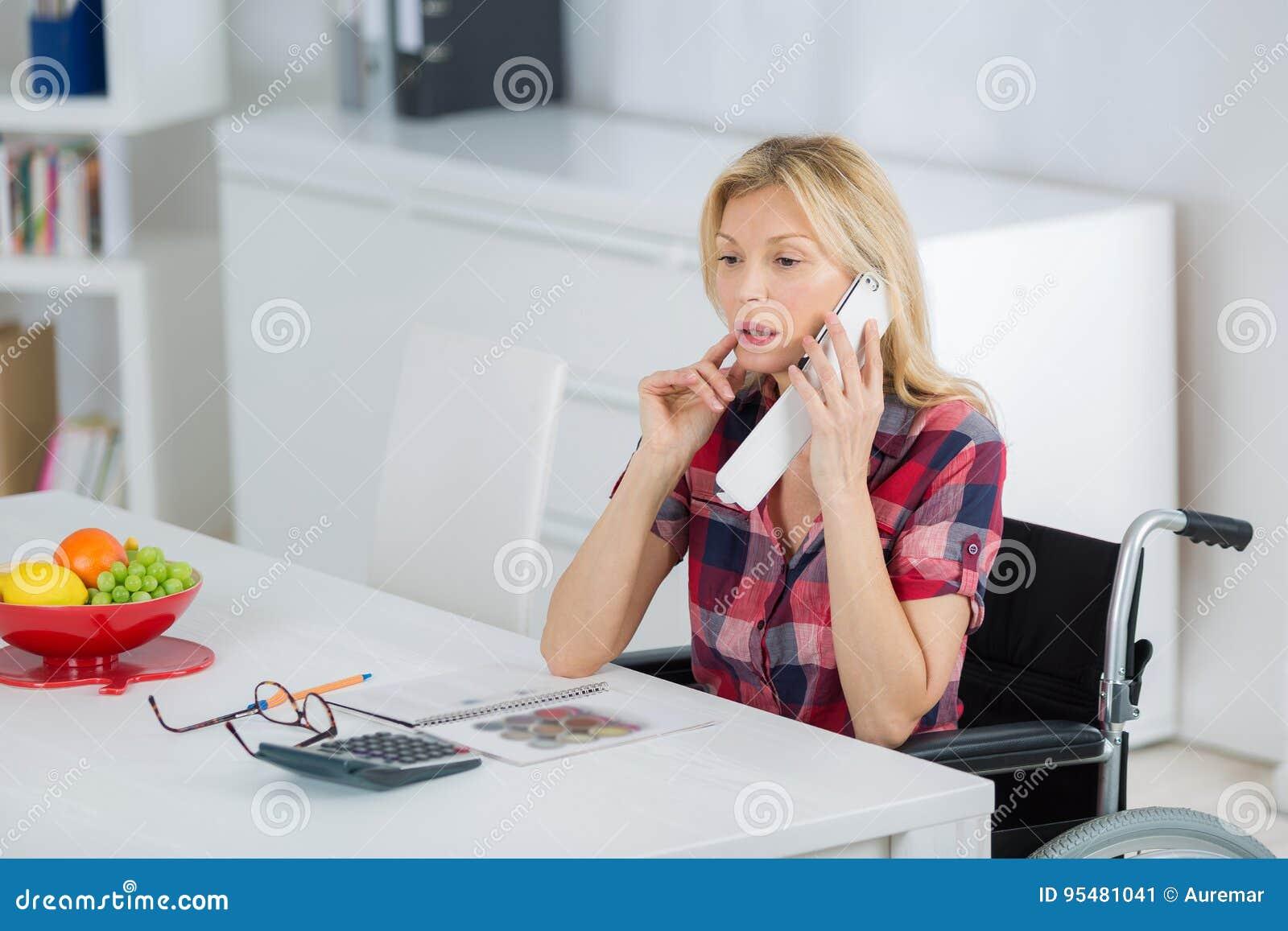Przypadkowy bizneswoman w wózku inwalidzkim na telefonie w biurze