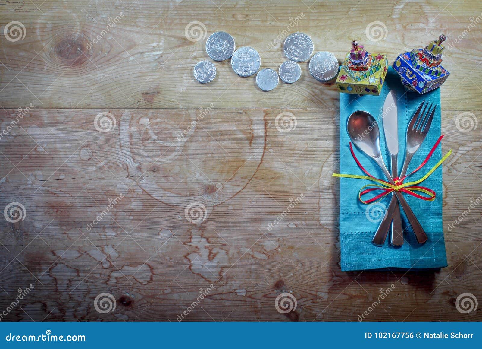 Przypadkowy Hanukkah miejsca obiadowy położenie z kolorową pieluchą, dreidels i gelt na starym drewno stole,
