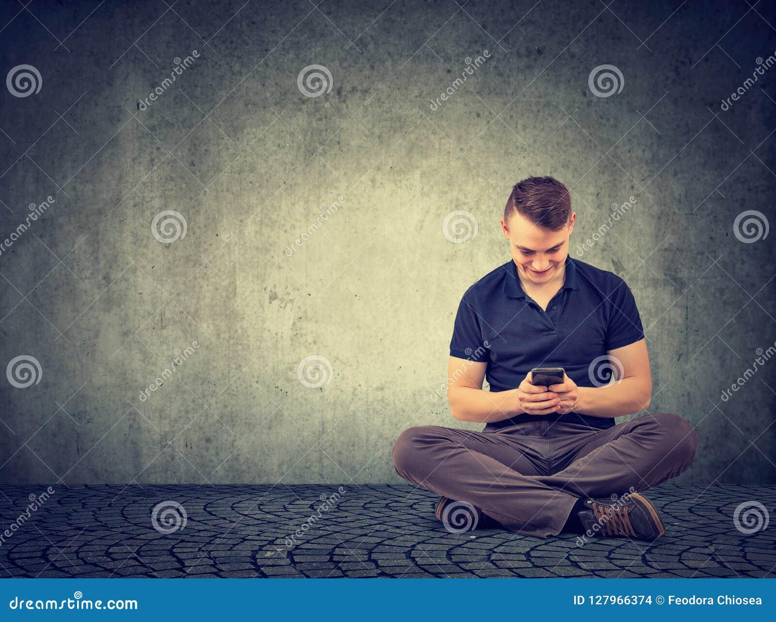 Przypadkowy mężczyzna używa smartphone podczas gdy siedzący