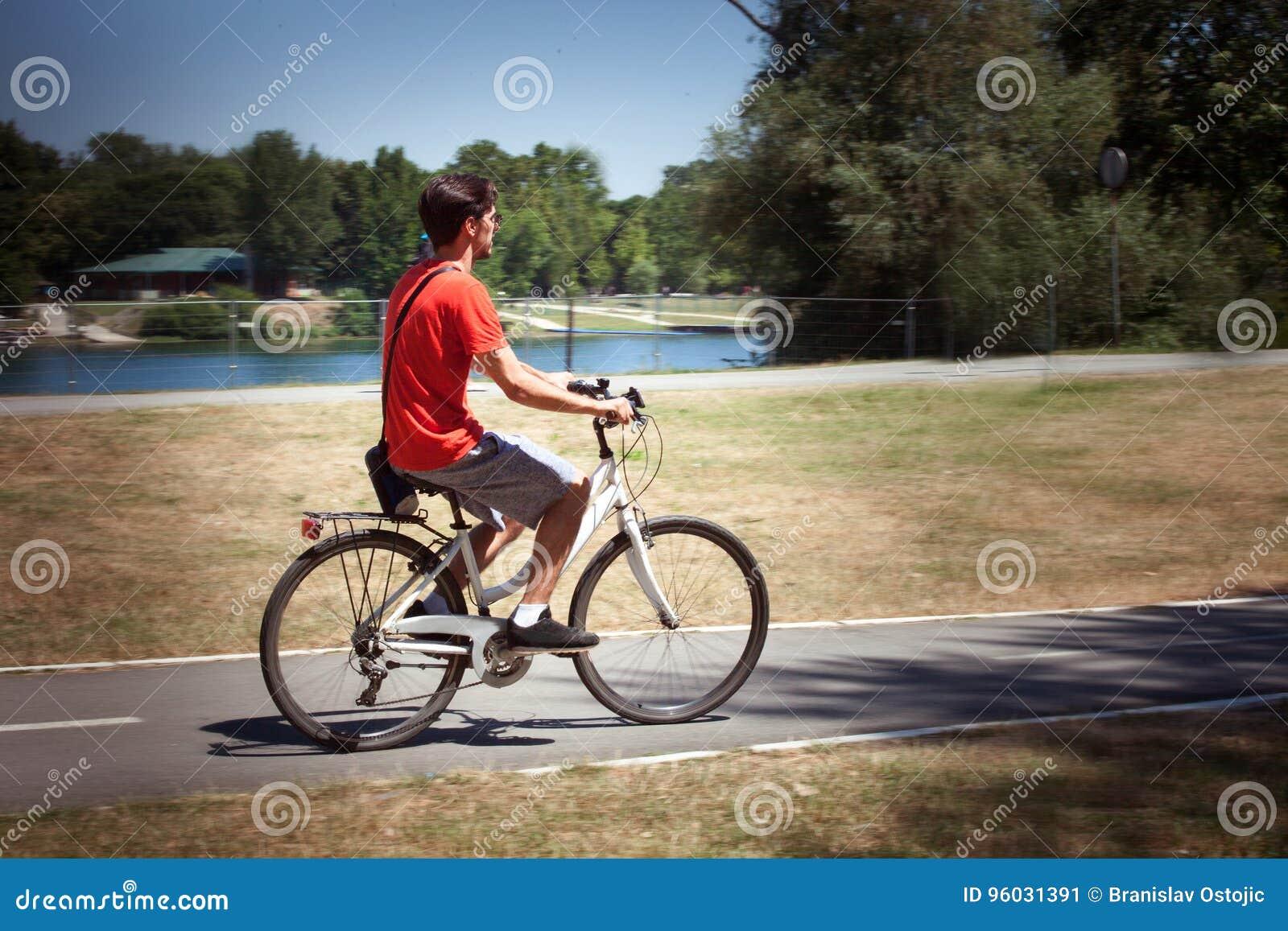 Przypadkowy młody człowiek przejażdżki rower jeziornym letnim dniem