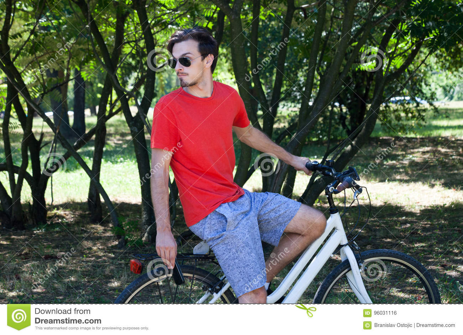 Przypadkowy młody człowiek z okularami przeciwsłonecznymi na roweru odpoczywać