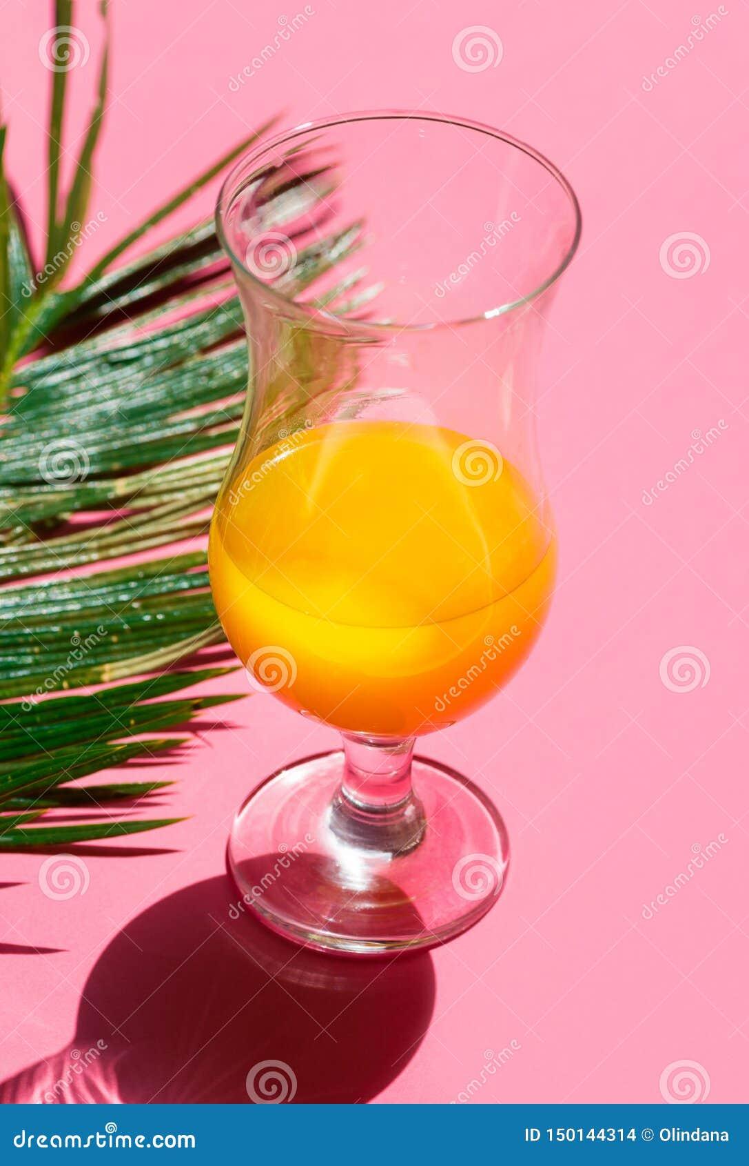 Przyrodni pełny koktajlu szkło z świeżej tropikalnej cytrus owoc soku zieleni palmowym liściem na modnym fuksji menchii tle Lato