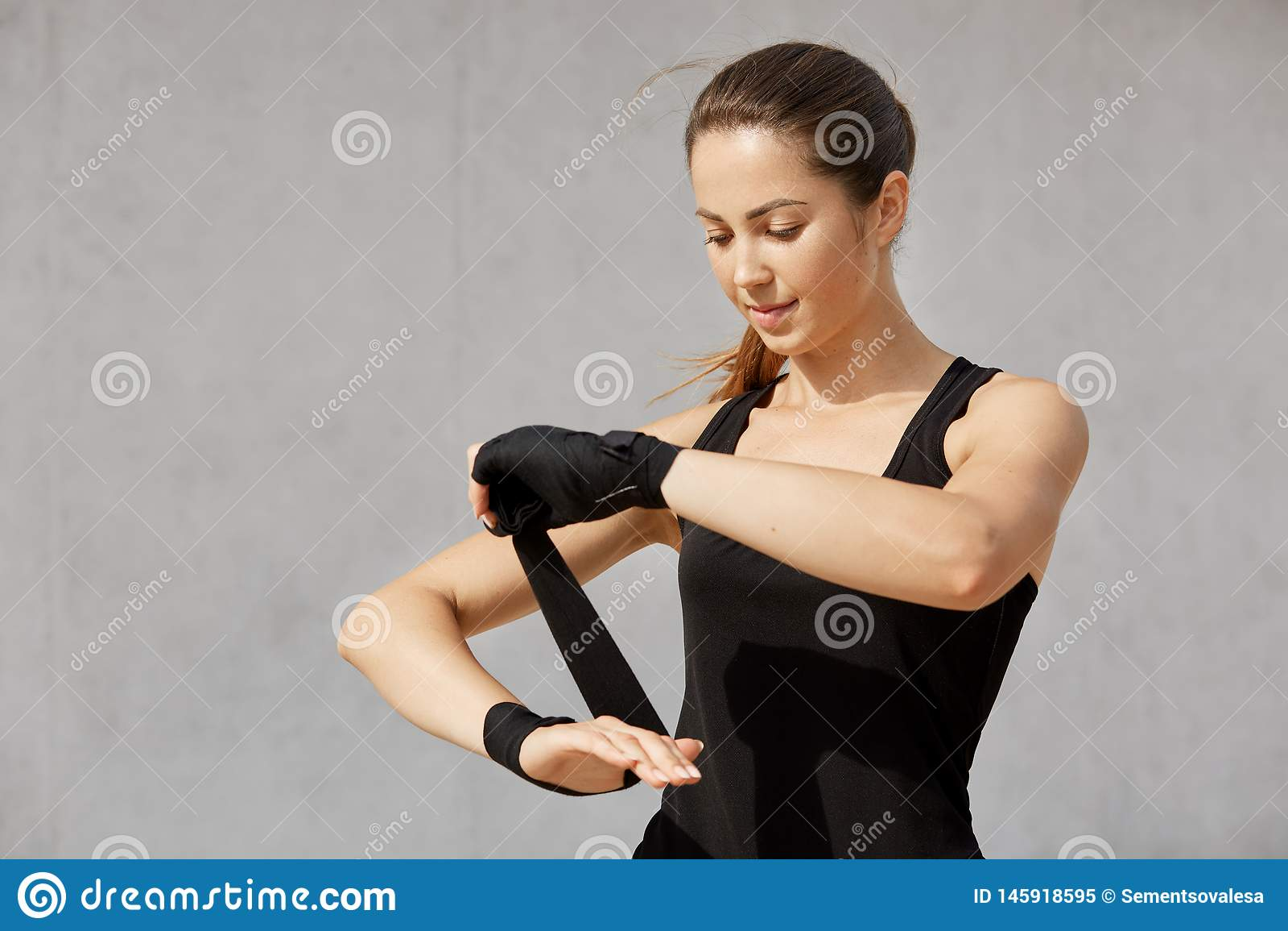Przyrodnia długości fotografia brunetki sporty kobieta z ponytail, jest ubranym czarnego strój, opakunkowy nadgarstku bandaż, sto