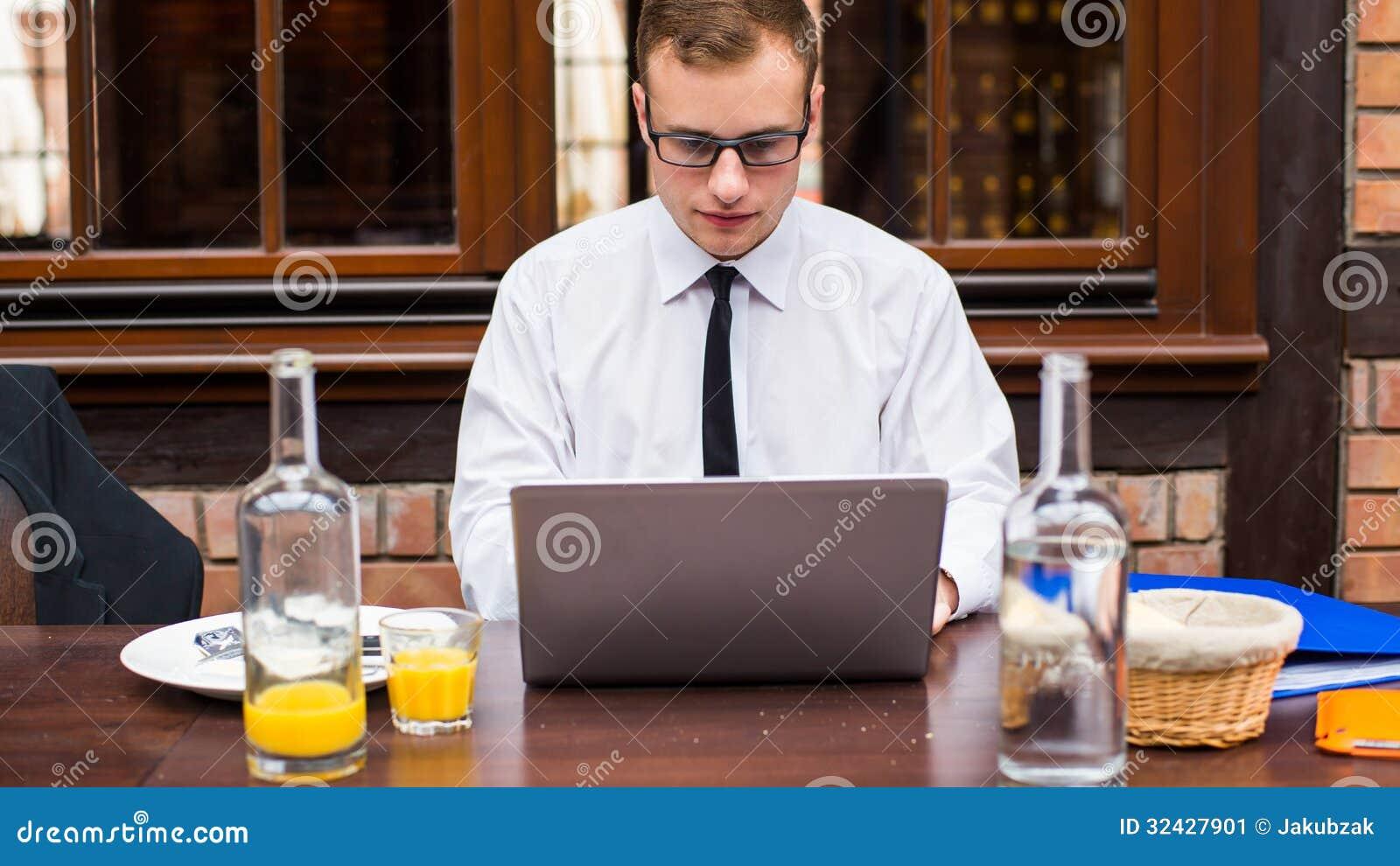 Przystojna biznesmen praca przy laptopem w restauraci.