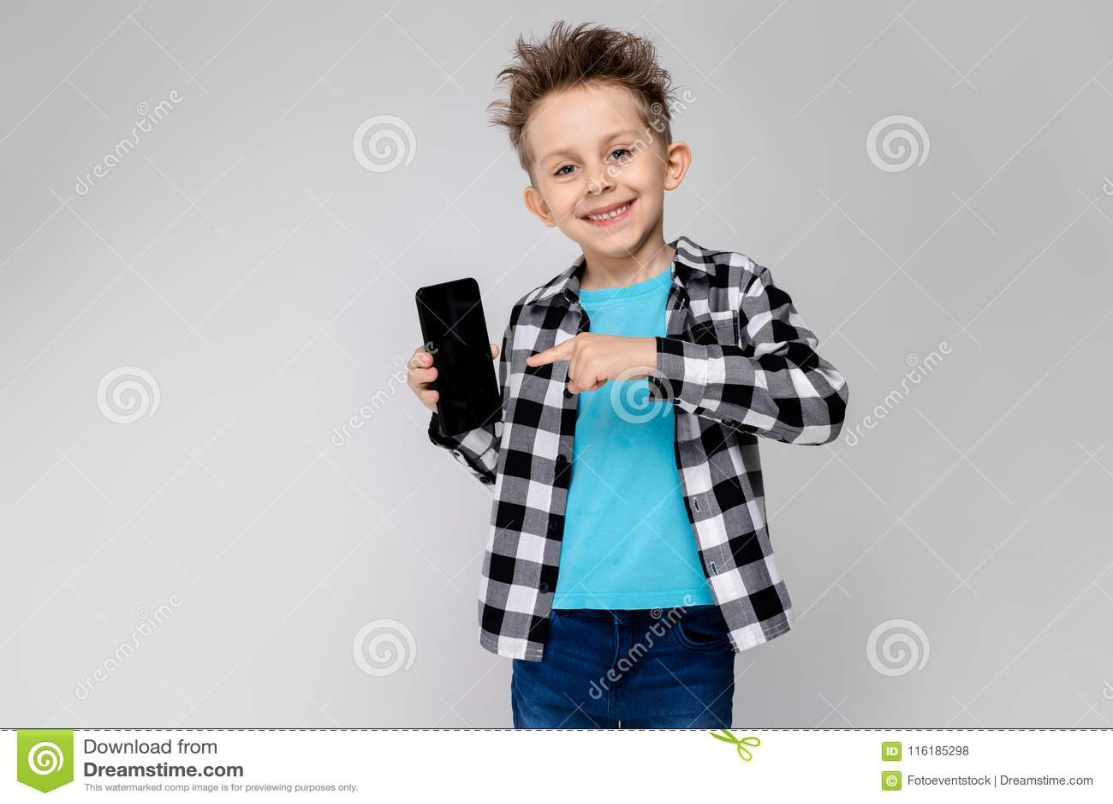 Przystojna chłopiec w szkockiej kraty koszula, błękitnej koszula i cajgów stojakach na szarym tle, Chłopiec trzyma telefon