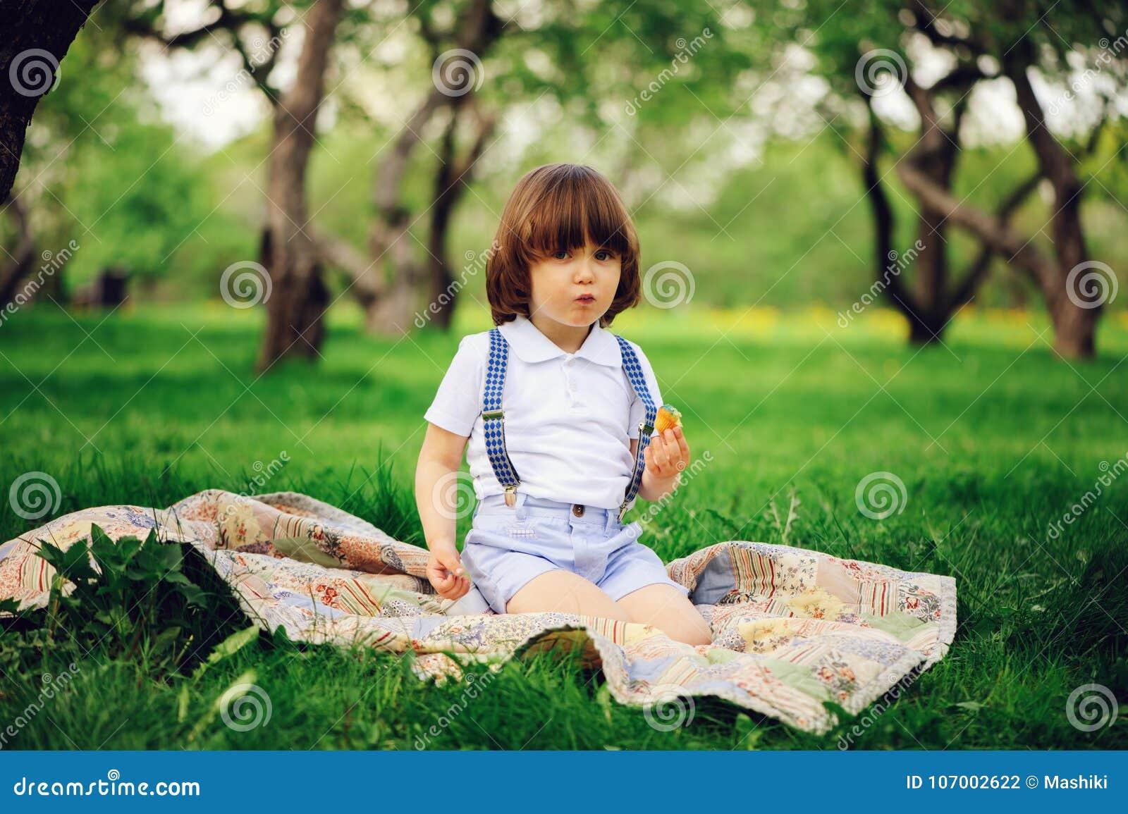 Przystojna elegancka 3 lat berbecia dziecka chłopiec z śmieszną twarzą w suspenders cieszy się cukierki na pinkinie
