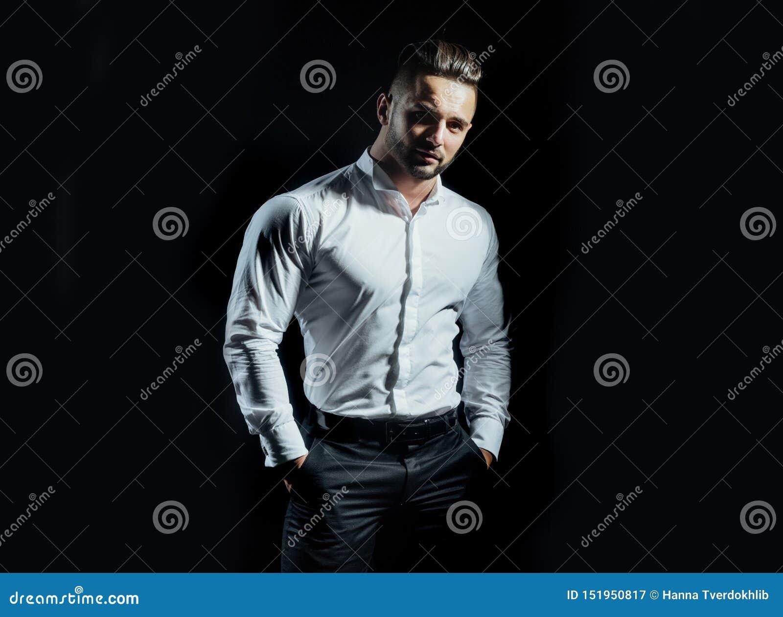 Przystojna mężczyzna pozycja z rękami w kieszeniach odizolowywać na czarnym tle Przystojna ufna młody człowiek pozycja i