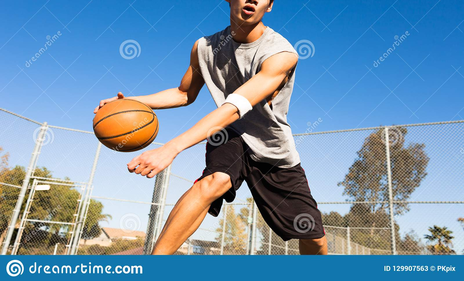 Przystojna męska bawić się koszykówka plenerowa