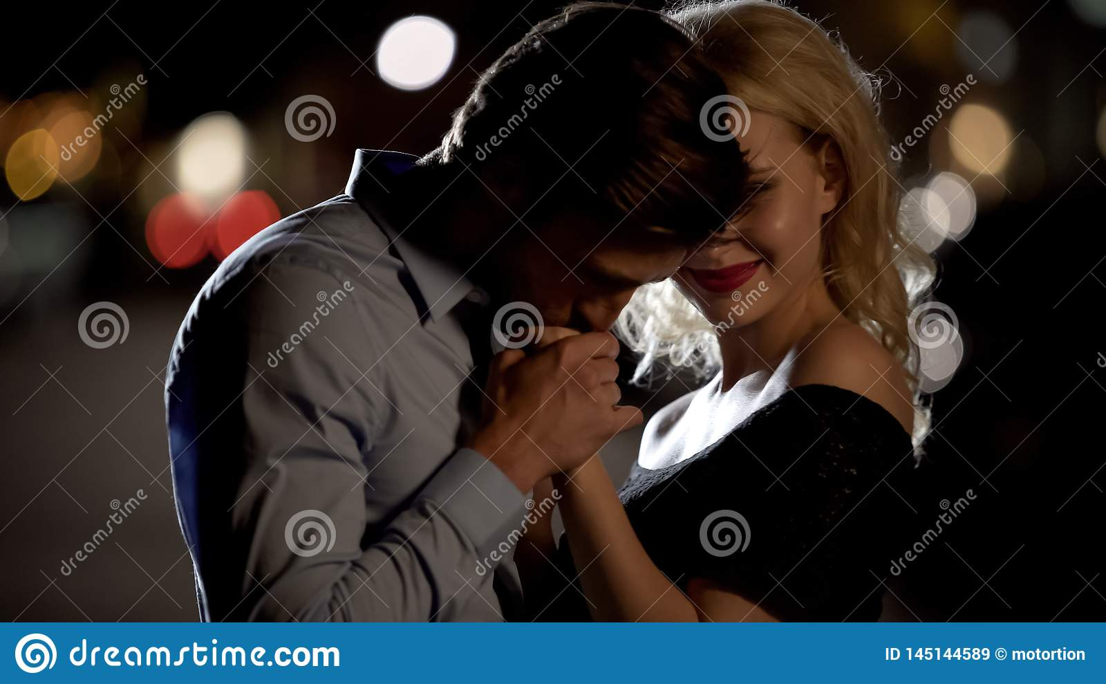 Przystojna męska całowanie kobiety ręka tenderly, mężczyzna kusi ładnej blondynki, data