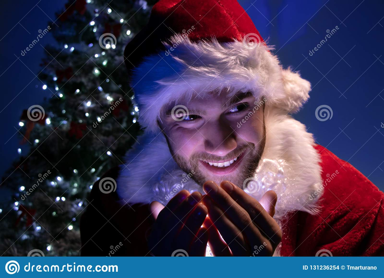 Przystojna samiec Santa uśmiecha się światła w jego ręce z choinką w tle i trzyma
