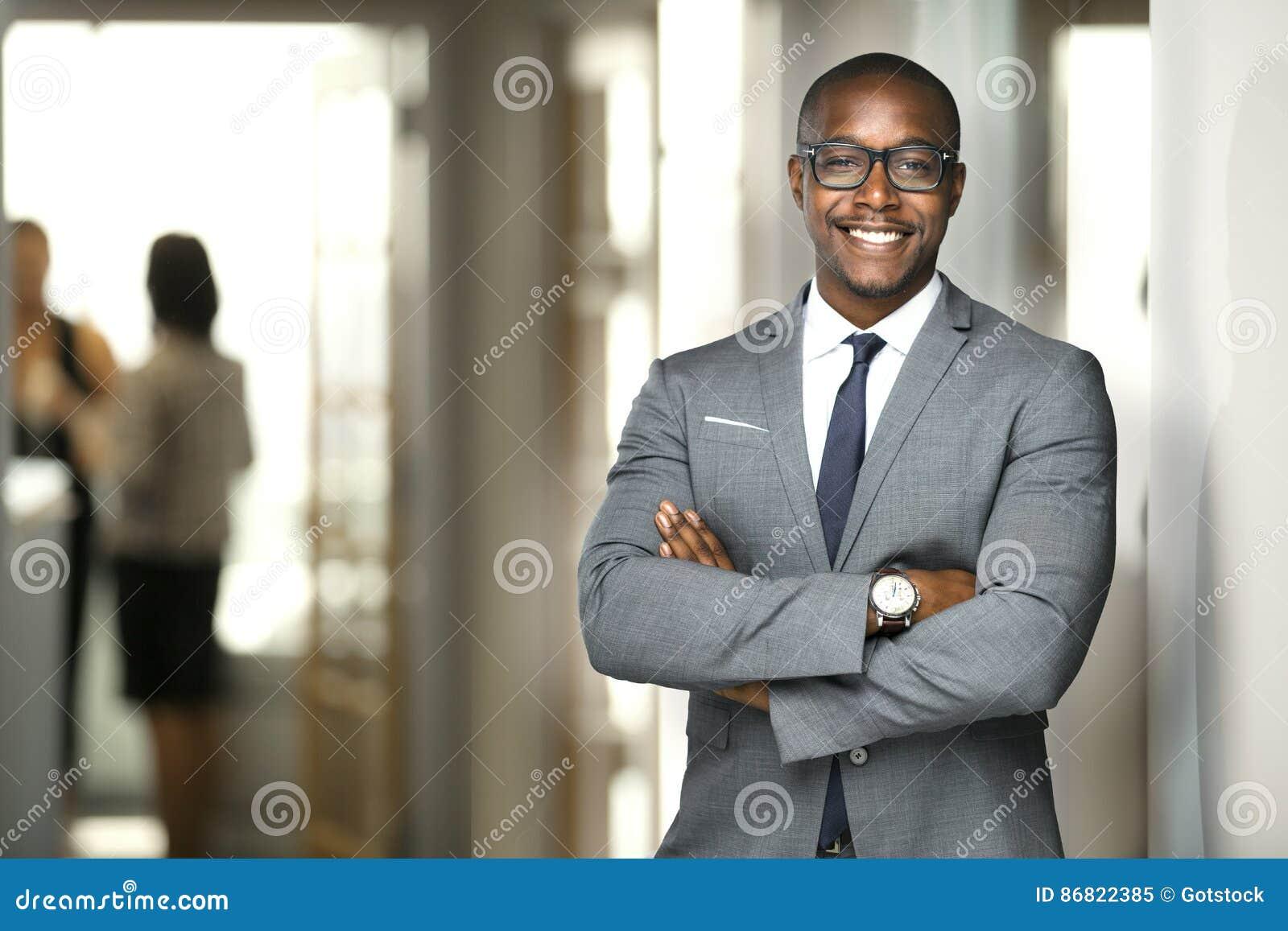 Przystojnego rozochoconego amerykanina afrykańskiego pochodzenia wykonawczy biznesowy mężczyzna przy workspace biurem