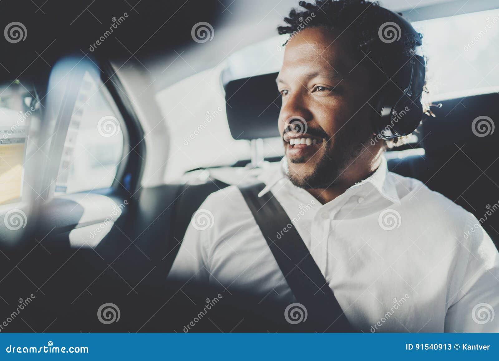 Przystojnego uśmiechniętego afrykańskiego mężczyzna słuchająca muzyka na smartphone podczas gdy siedzący na tylnym siedzeniu w ta