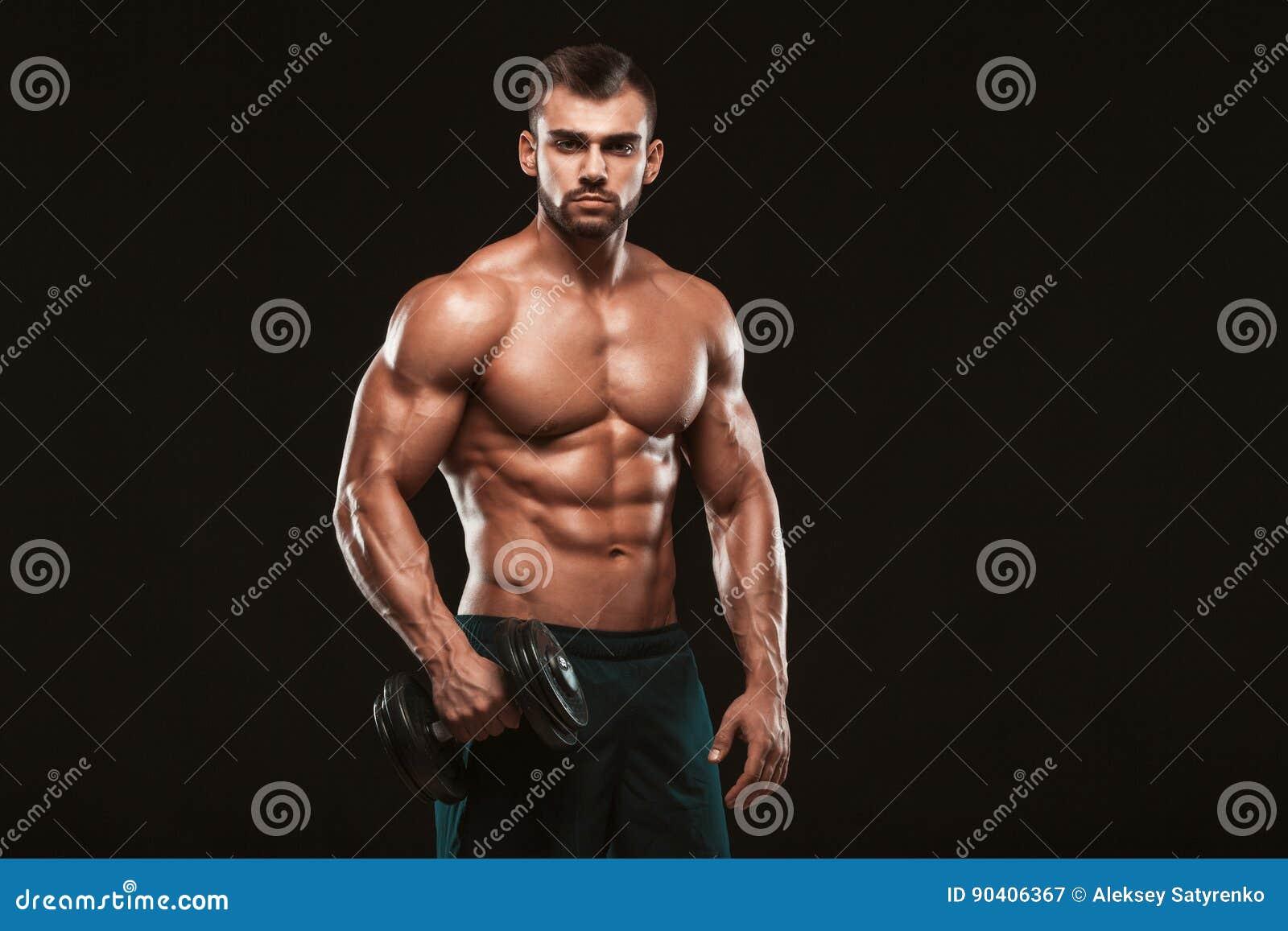 Przystojnej władzy sportowy mężczyzna pompuje up mięśnie z dumbbells w gym w szkoleniu Sprawności fizycznej mięśniowy ciało odizo