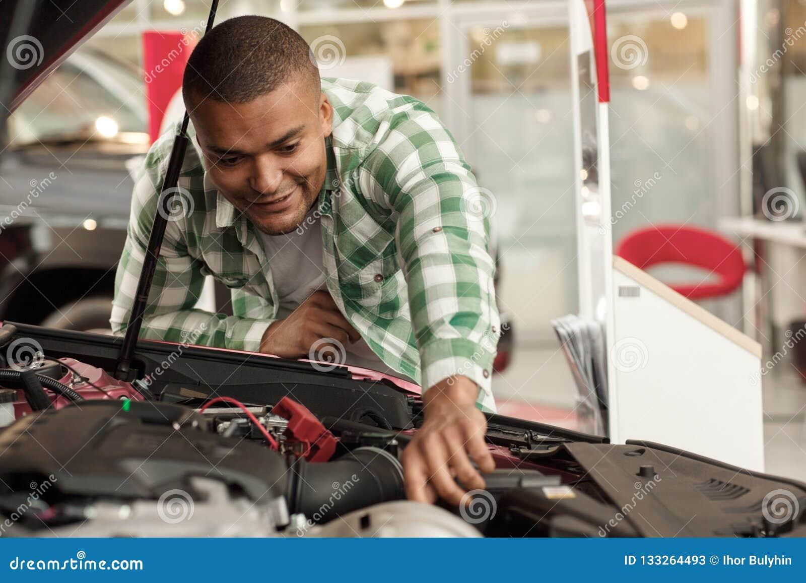 Przystojny Afrykański mężczyzna wybiera nowego samochód przy przedstawicielstwem handlowym
