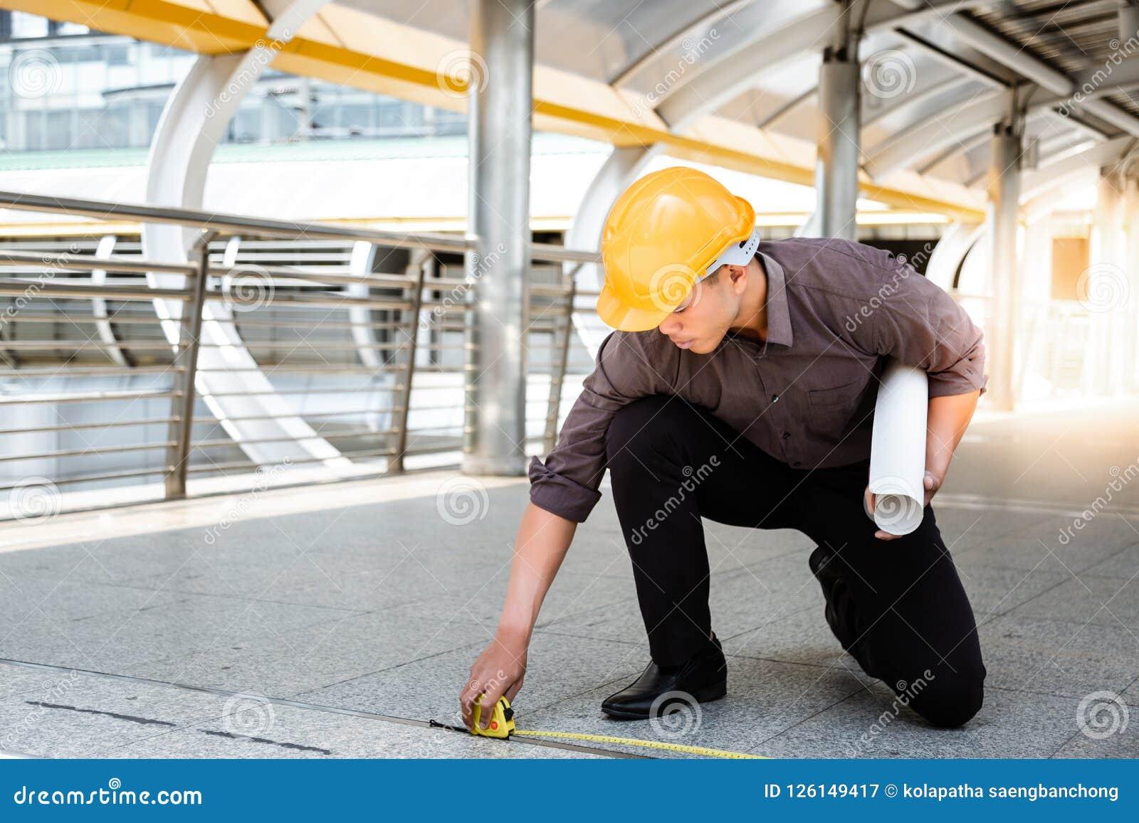 Przystojny azjatykci pracownika lub inżyniera mężczyzna mierzy podłoga obok