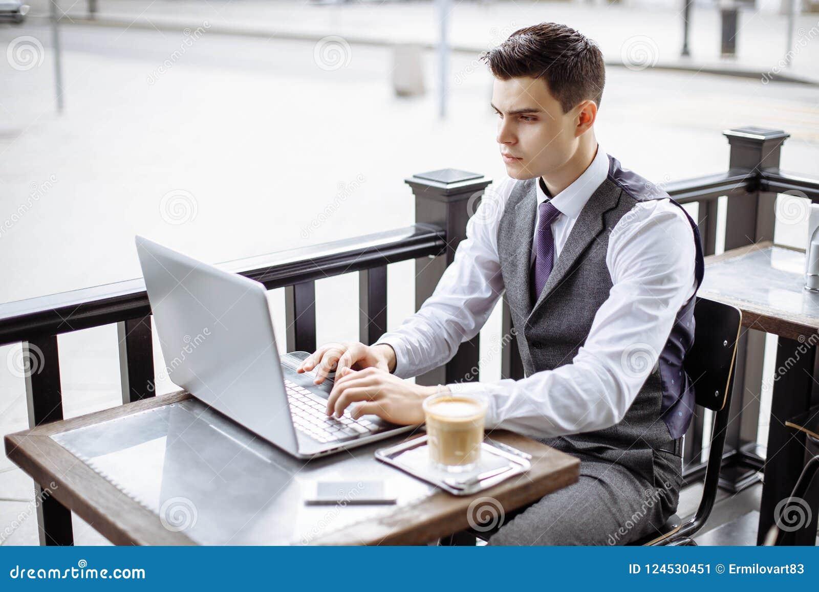 Przystojny biznesmen jest ubranym kostium i używa outdoors nowożytnego laptop, pomyślnego kierownika pracuje podczas przerwy i sz