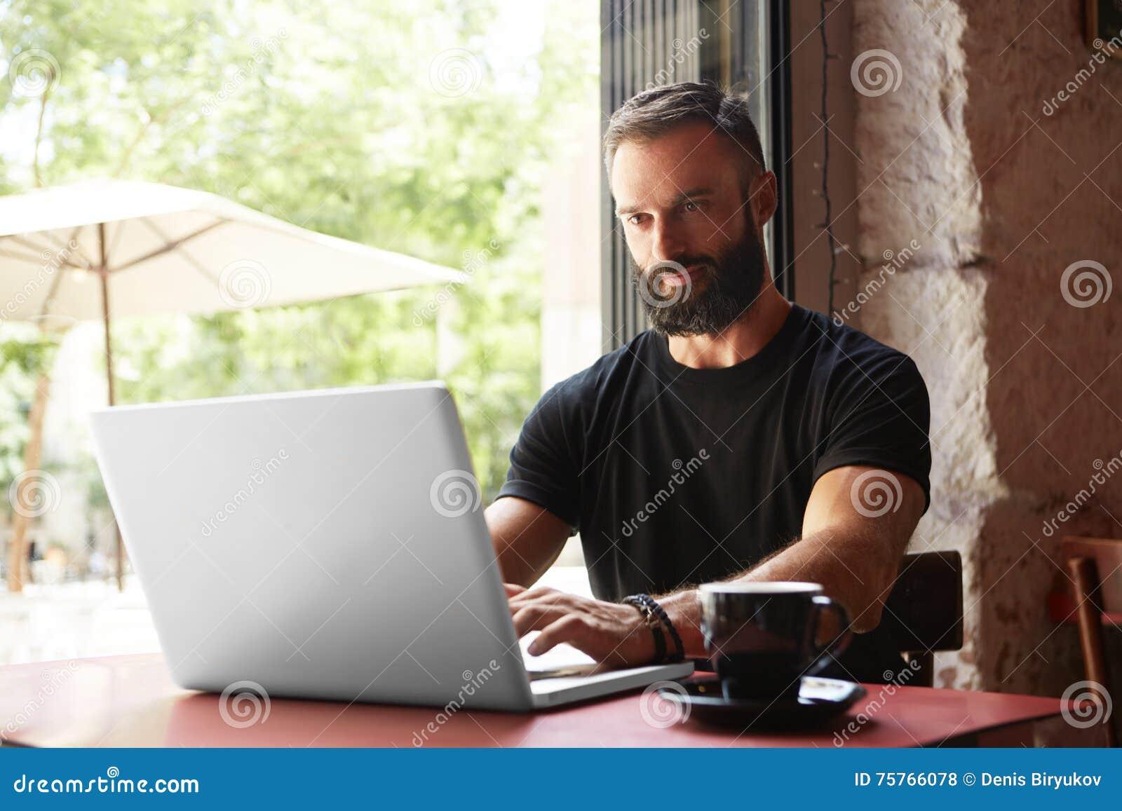 Przystojny Brodaty biznesmen Jest ubranym Czarnego Tshirt laptopu drewna Pracującego stołu Miastowej kawiarni Młody kierownik pra