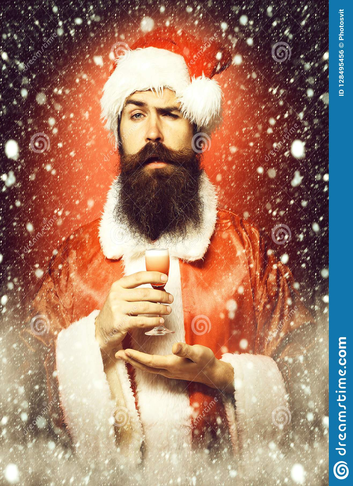 Przystojny brodaty Santa Claus mężczyzna trzyma szkło alkoholiczka strzał na ręce w bożych narodzeniach z długą brodą na poważnej