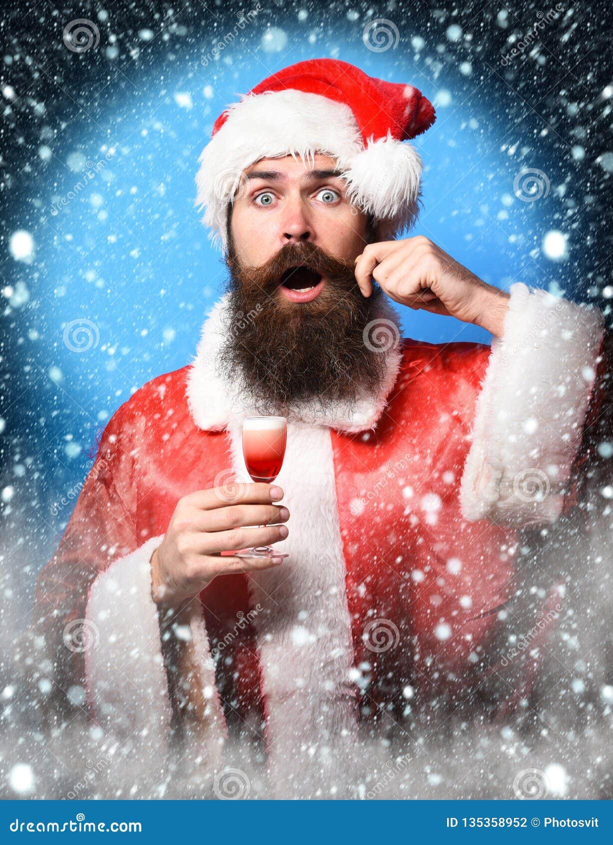 Przystojny brodaty Santa Claus mężczyzna trzyma szkło alkoholiczka z długą brodą na zdziwionej twarzy strzelał w bożych narodzeni