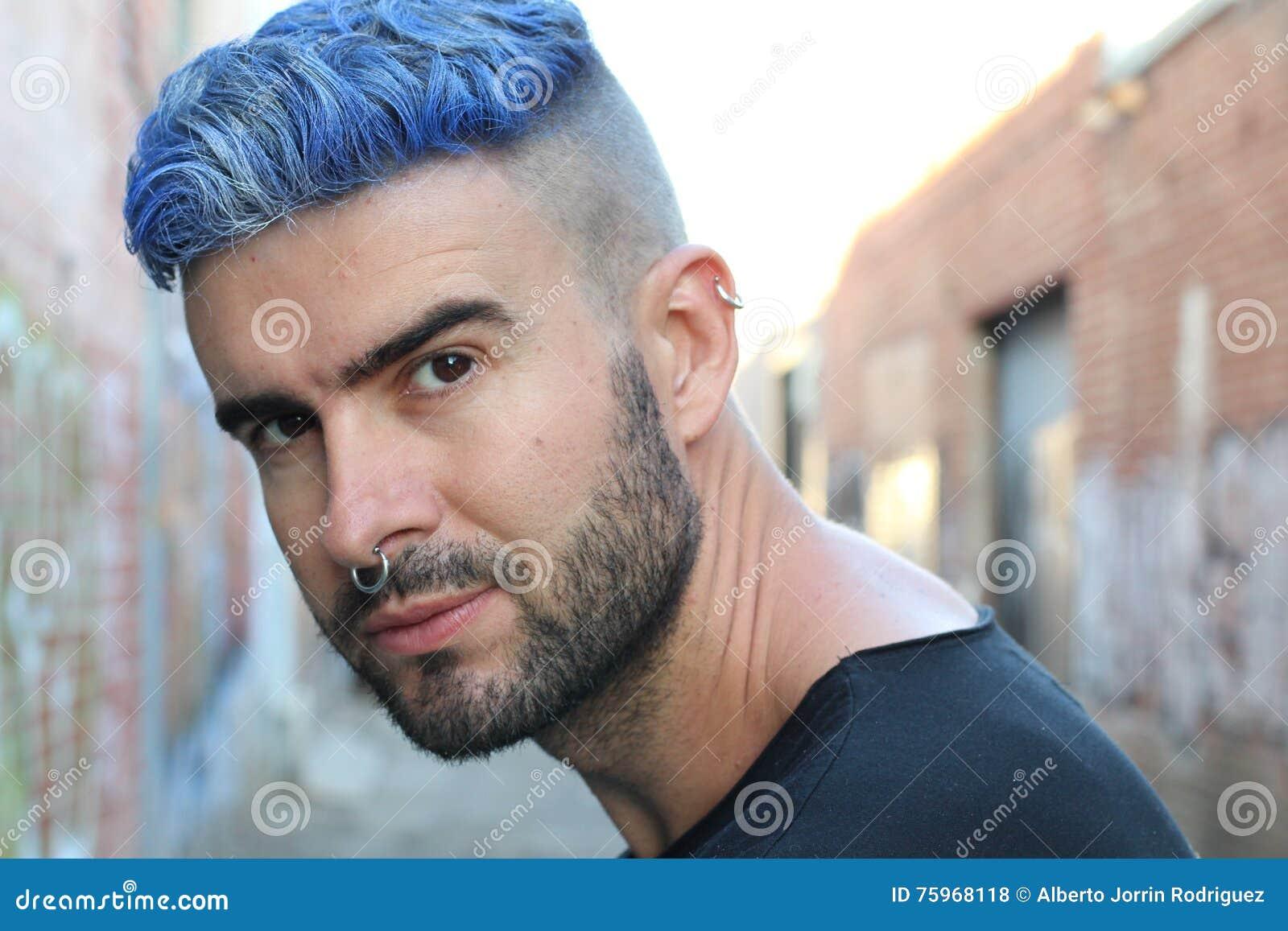 Przystojny elegancki młody człowiek z sztucznie barwiony błękit farbującym włosy podcinał fryzurę, brodę i piercings z kopii prze