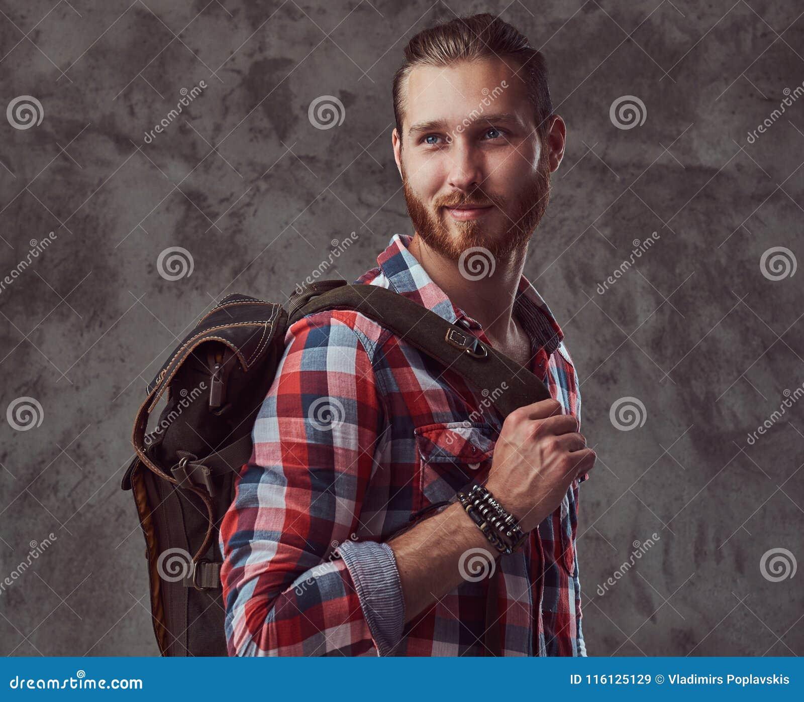 Przystojny elegancki rudzielec podróżnik w flanelowej koszula z plecakiem, pozuje w studiu na szarym tle