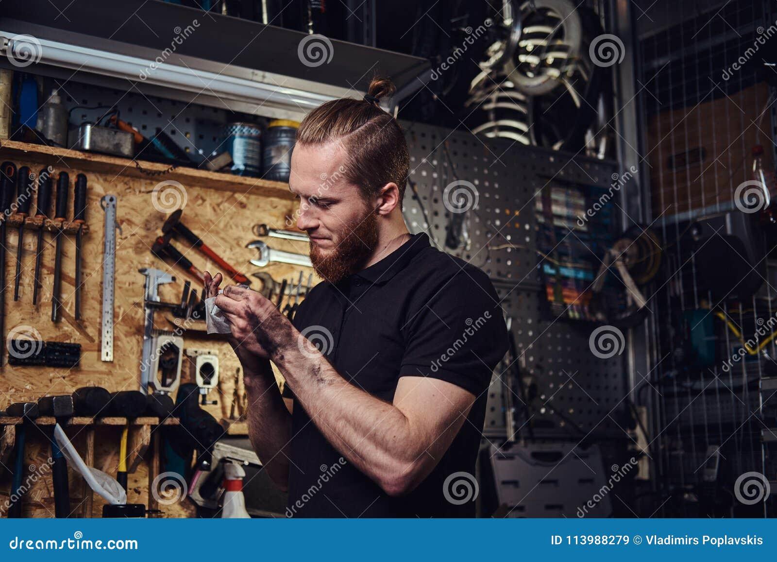 Przystojny elegancki rudzielec pracownik, czyści jego brudne ręki po naprawiać pracować w warsztacie