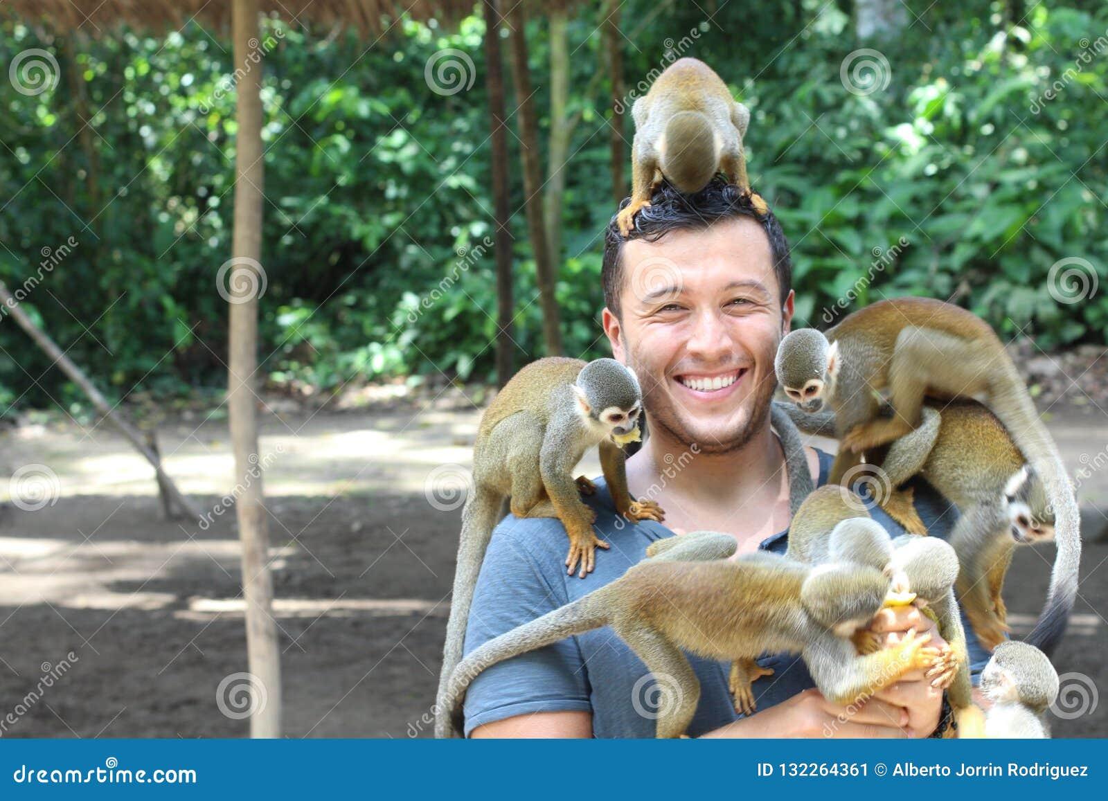 Przystojny etniczny mężczyzna z titi małpami