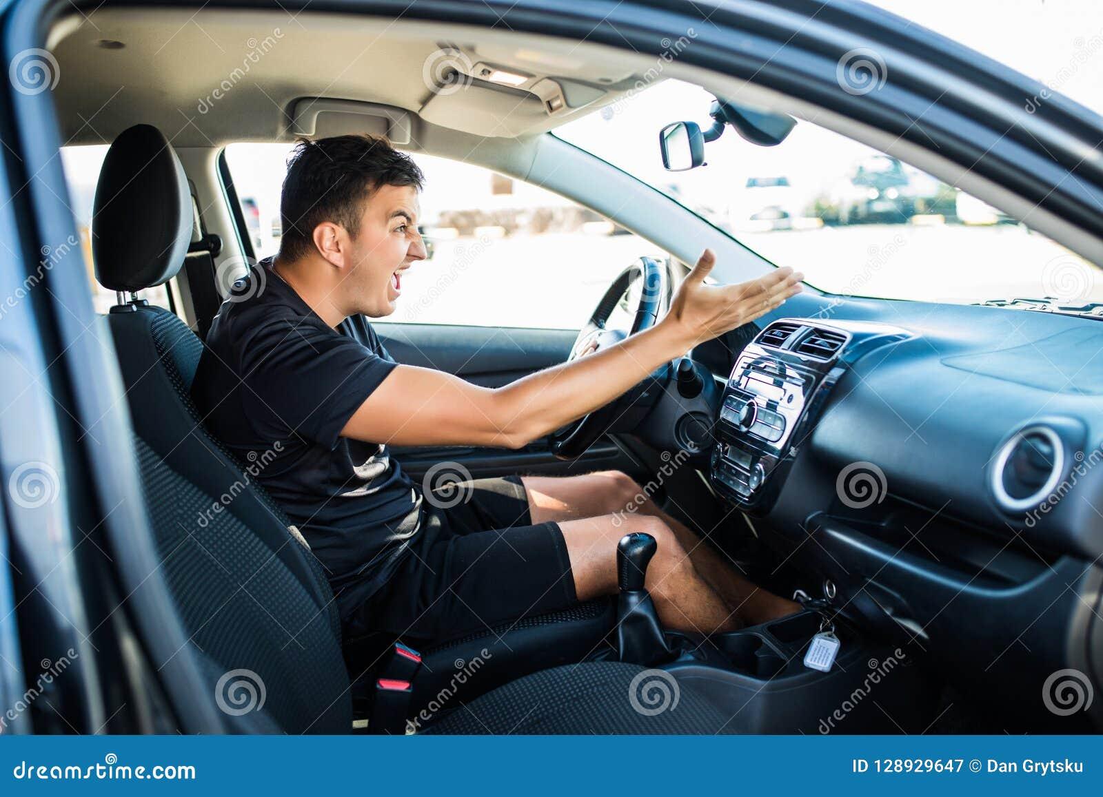 Przystojny gniewny kierowca podczas gdy prowadnikowy samochód w mieście Negatywny ludzki emoci twarzy wyrażenie