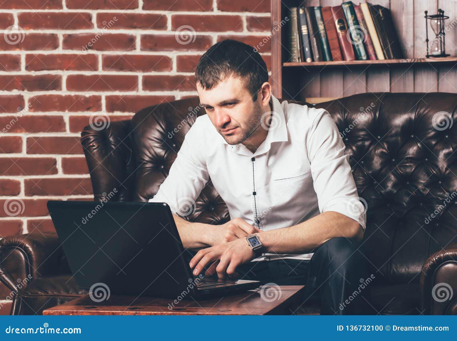 Przystojny mężczyzna czyta informację w laptopie na tle półka z książkami Biznesmen siedzi na miękkiej kanapie w jego