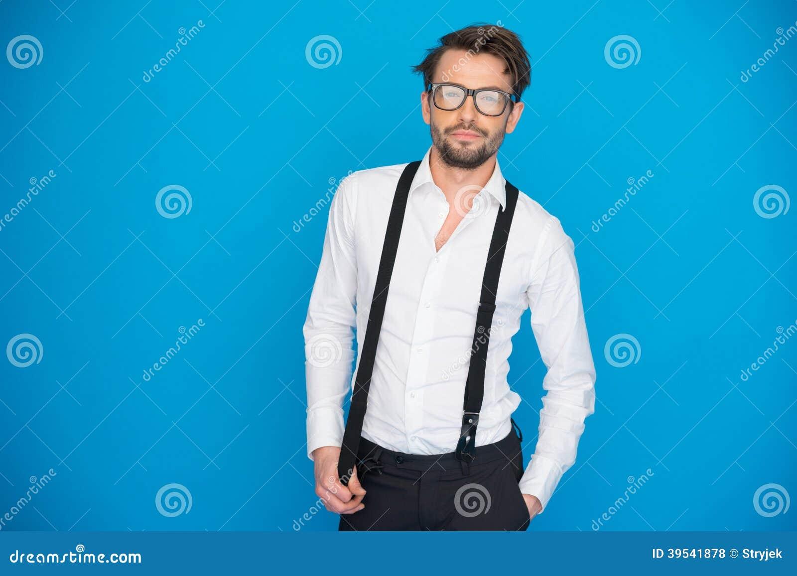 Przystojny mężczyzna jest ubranym białych brasy i koszula na błękicie