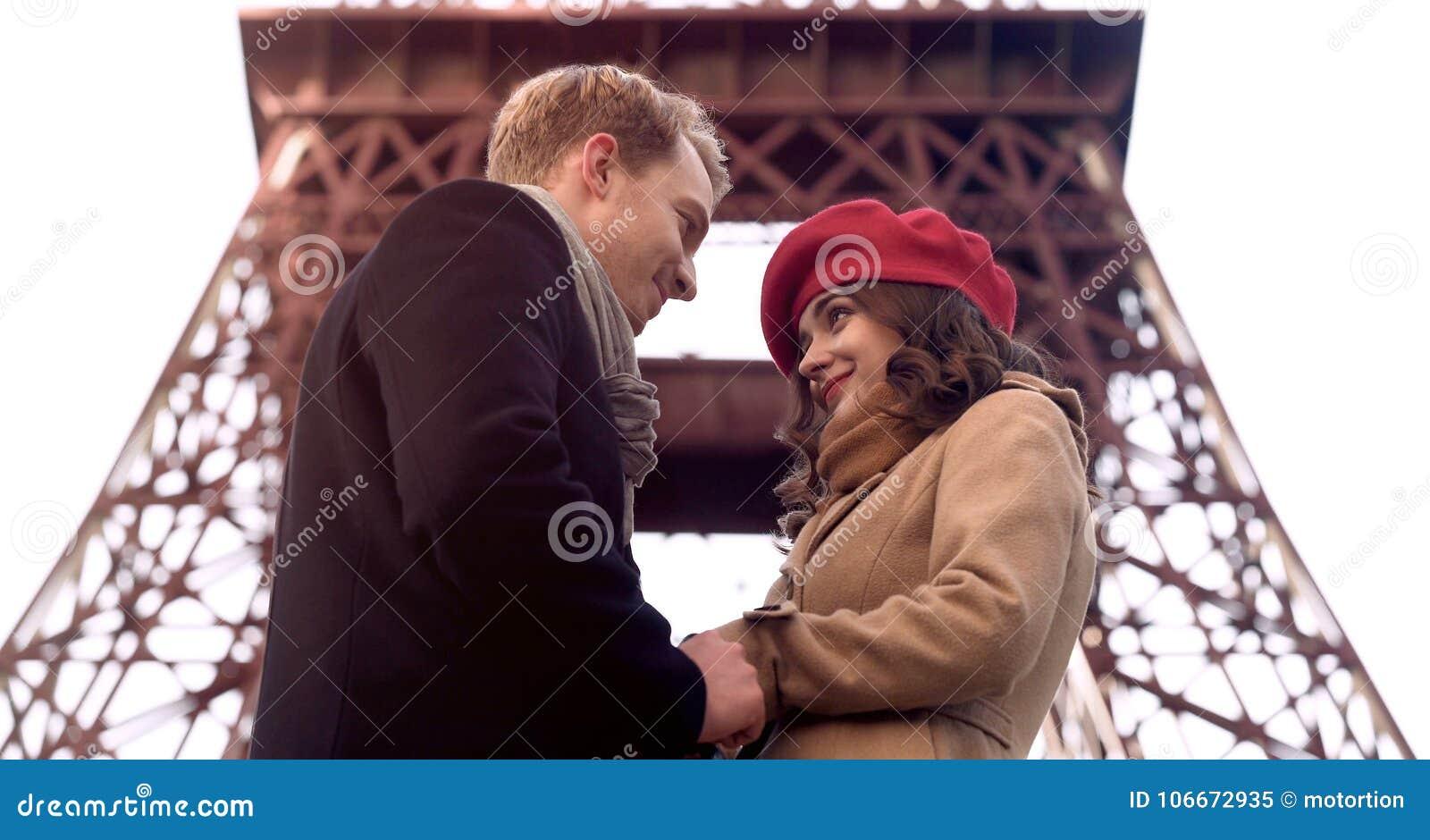 Przystojny mężczyzna patrzeje pięknej kobiety z miłością, pierwszy data, romans w Paryż