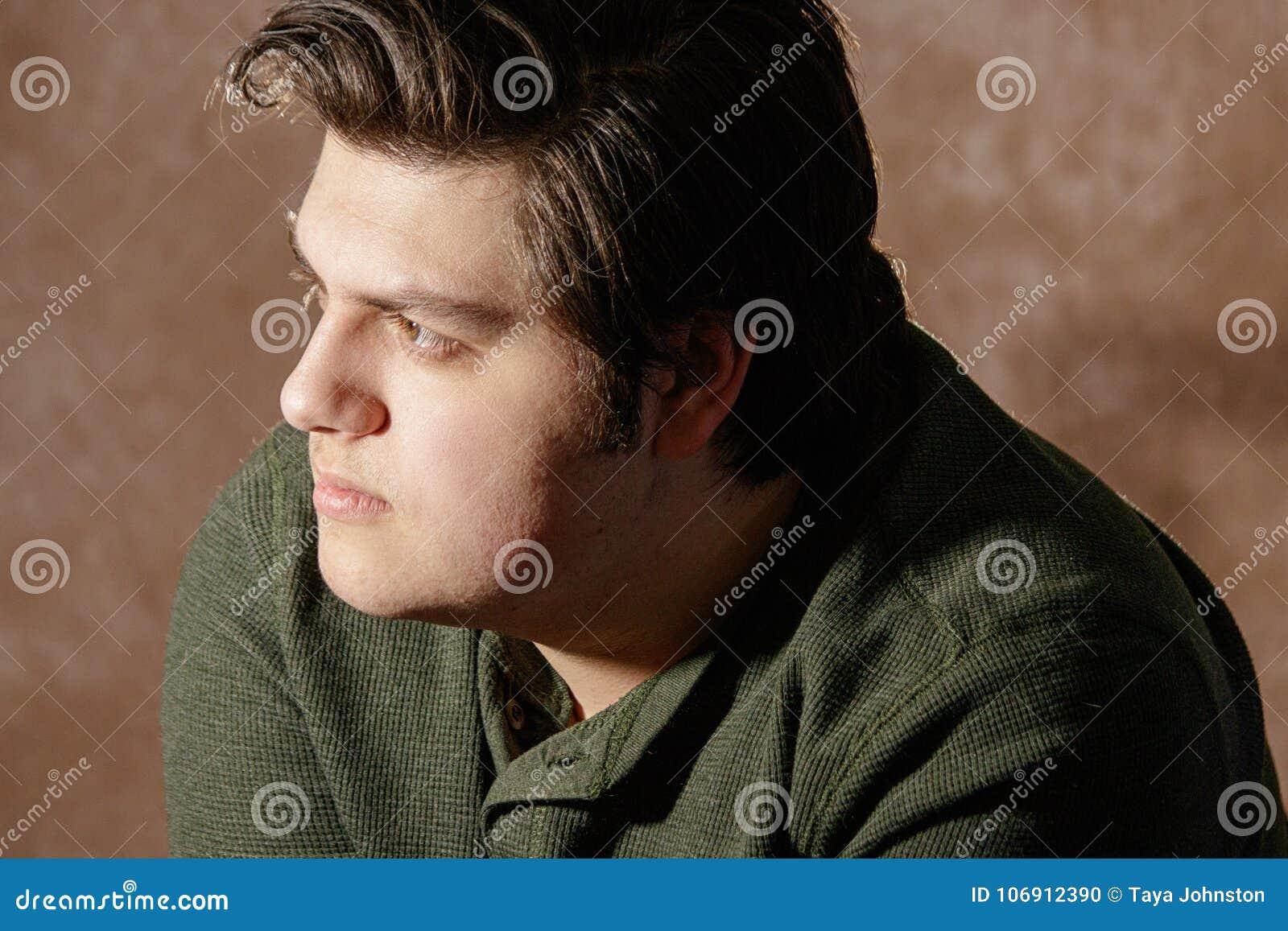 Przystojny mężczyzna profil patrzeje przestrzeń nad jasnobrązowym pracownianym tłem