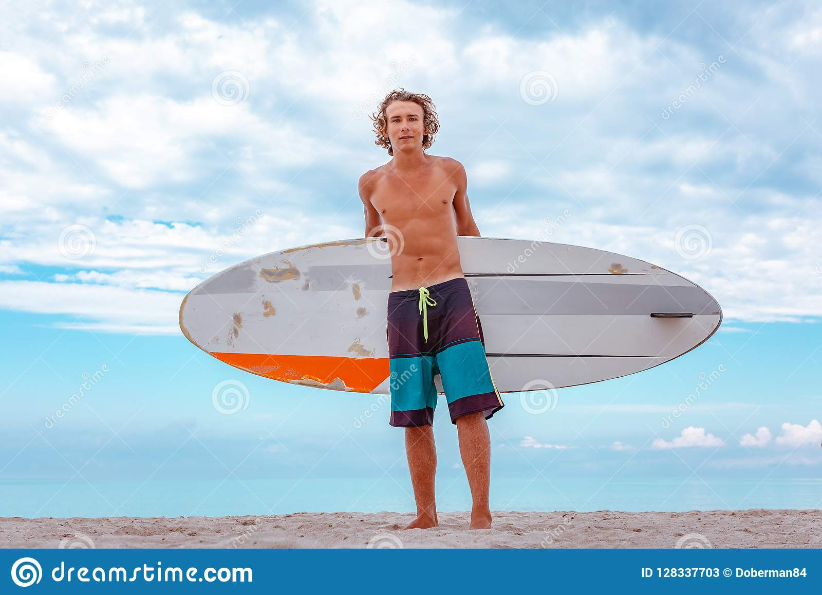 Przystojny mężczyzna spacer z białą pustą surfing deską czekać na fala surfować punkt przy dennym oceanu brzeg Pojęcie sport