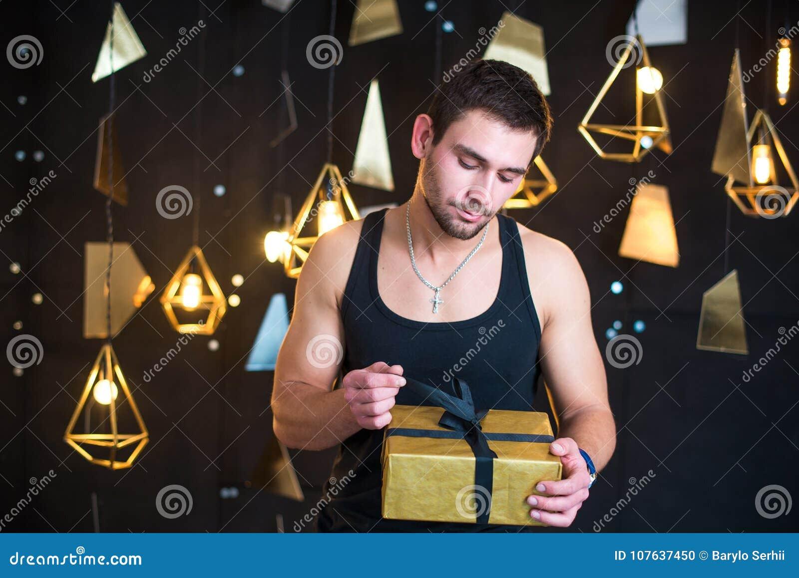 Przystojny mężczyzna w czarnym podkoszulku bez rękawów trzyma prezent w jej rękach, otwiera prezent, teraźniejszość