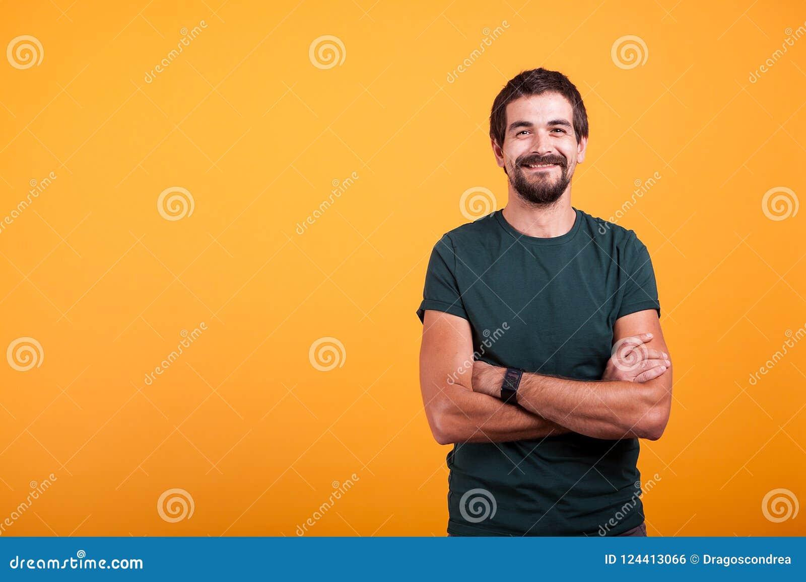 Przystojny mężczyzna z jego rękami krzyżował uśmiecha się przy kamerą