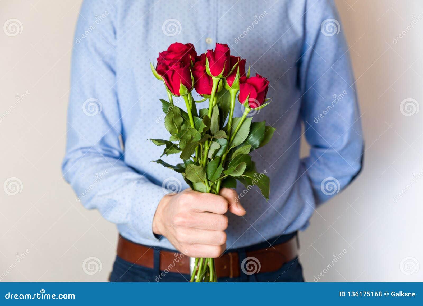 Przystojny młodego człowieka mienia czerwieni róży bukiet, romantyczna walentynka dnia niespodzianka, miłość, kwitnie