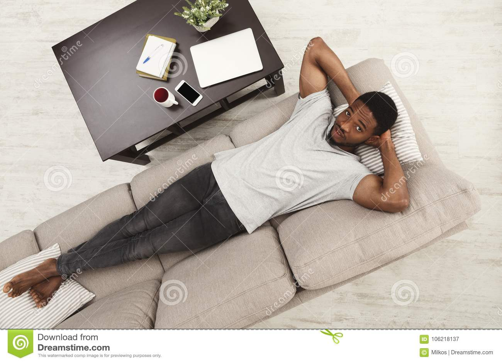 Przystojny młody afroamerykański mężczyzna relaksuje na leżance w domu