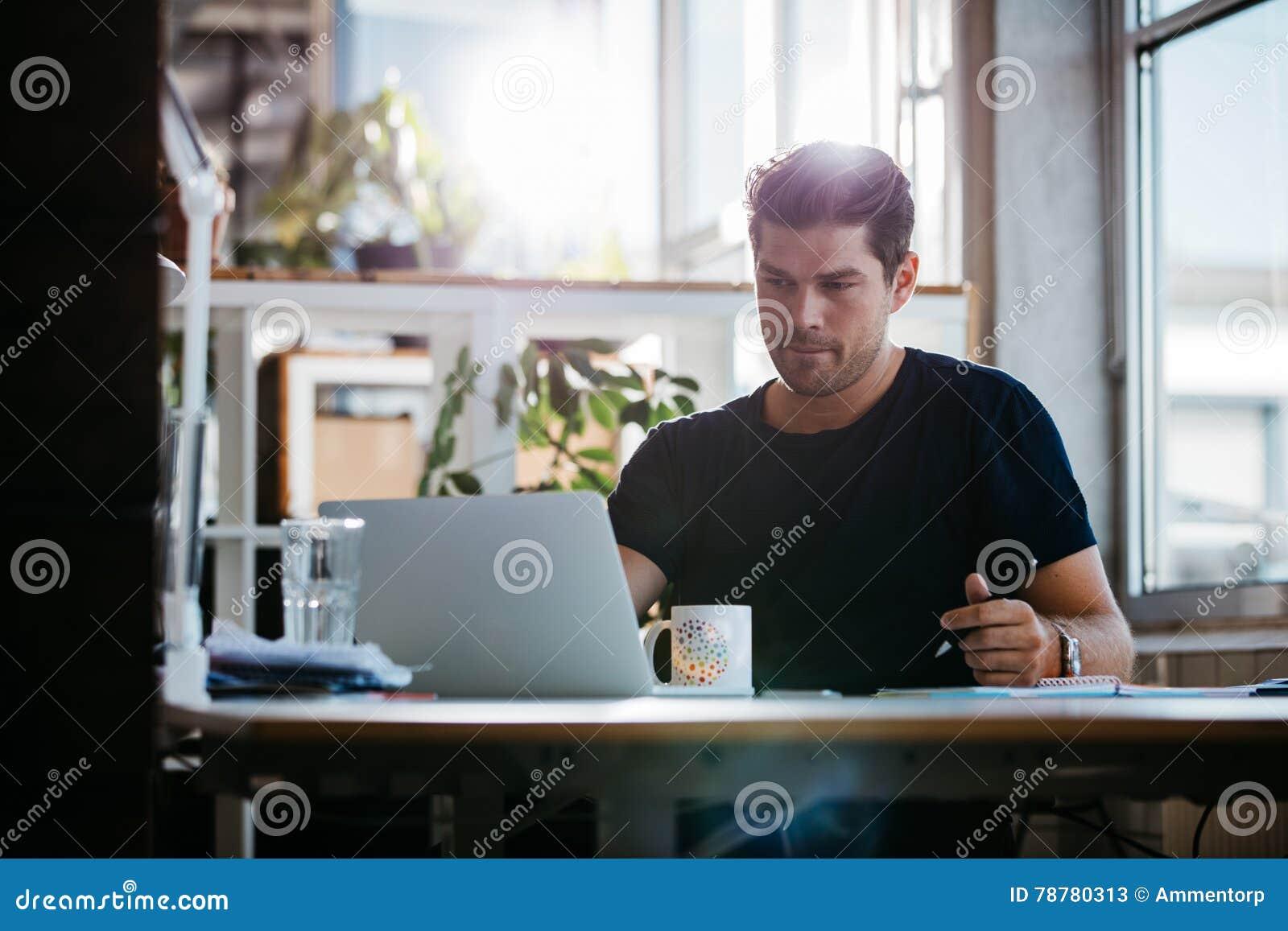 Przystojny młody biznesmen pracuje przy jego biurkiem