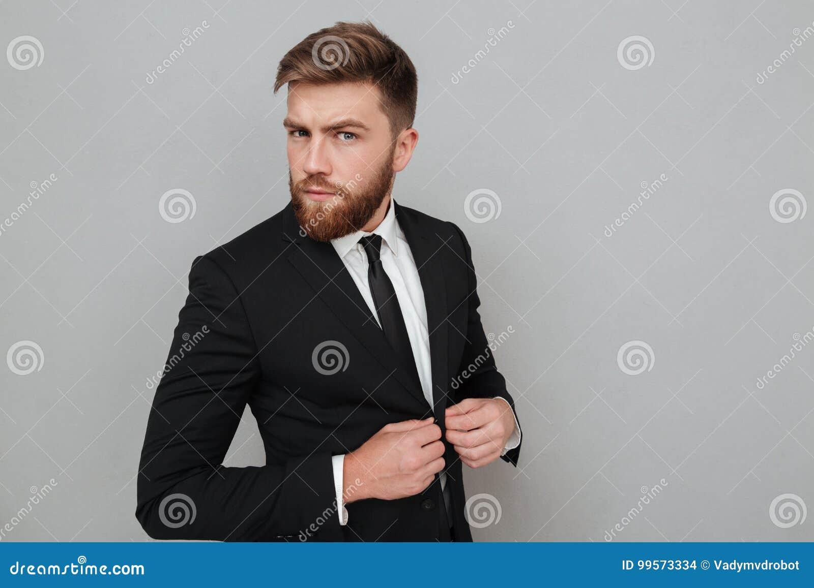 Przystojny młody biznesmen w kostiumu patrzeć kamerę i pozyci