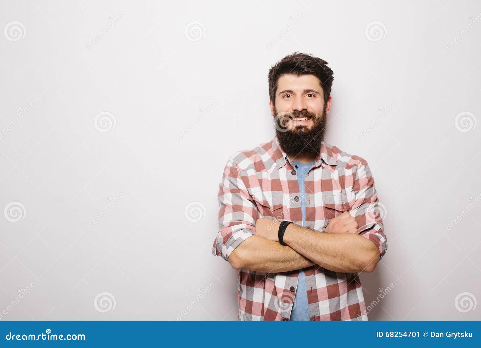 Przystojny młody brodaty mężczyzna mienie krzyżował ręki i patrzeć kamerę