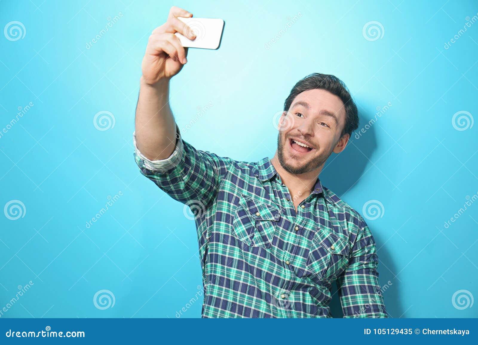Przystojny młody człowiek bierze selfie